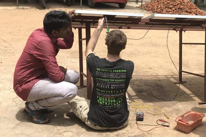 Two men add wiring to the underside of a table