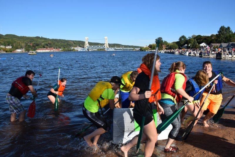 Students pulling a cardboard boat out of the water