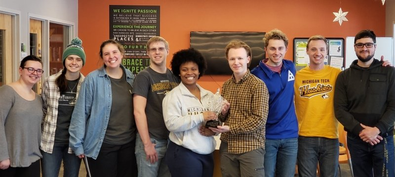 Members of the Undergraduate Student Advisory Board pose with a Winter Carnival statue trophy