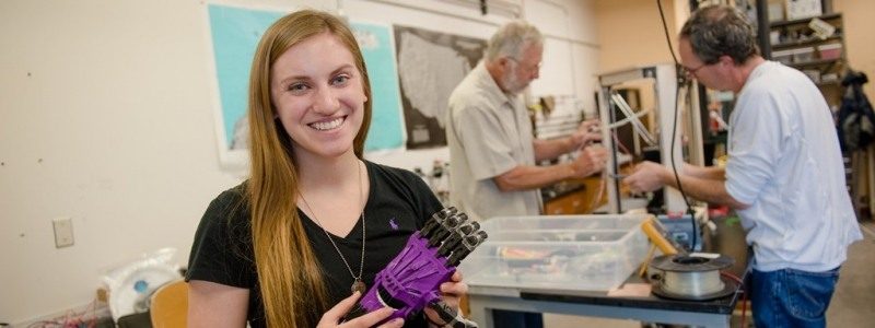 Female student in a lab holding a prosthetic hand.