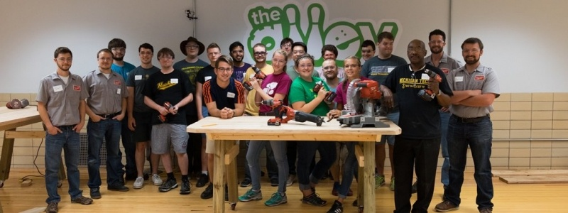 Group photo of students in the makerspace with a work table in front of them.