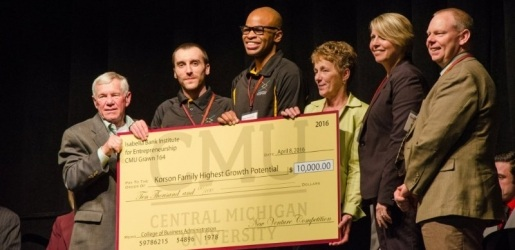 Staff from Central Michigan University and Michigan Technological University holding an oversize check from CMU.