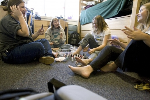 Students playing a game on the floor of their dorm room.
