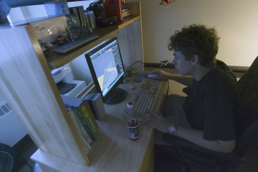 Student in his room, working on his computer.