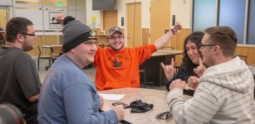 Five students sitting around a table, one has his arms raised in the air in celebration