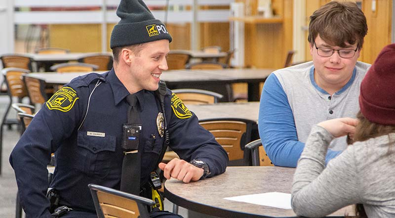 MTU public safety officer smiling while sitting with students