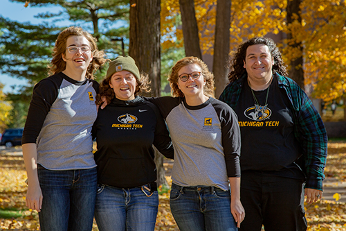 Four Residential Assistants posing in front of fall colors