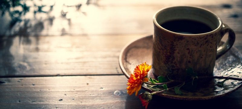 Coffee cup on table with flower