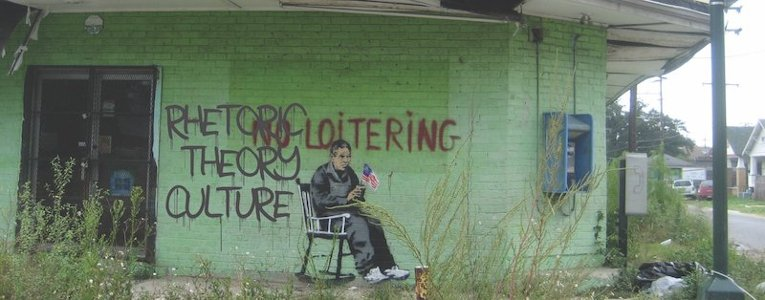 Rhetoric, Theory, Culture graphic on the side of a building with No Loitering spraypainted and the painted image of an elderly man sitting a rocking chair holding the U.S. flag
