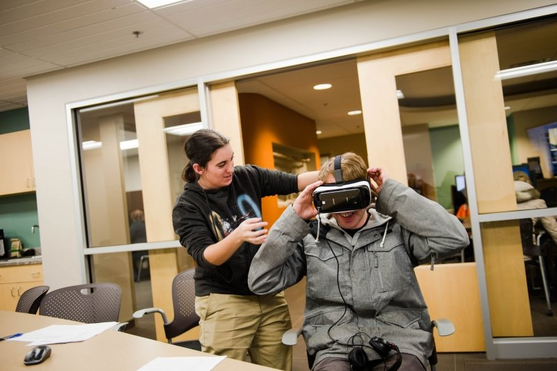 A research student adjusting the virtual reality headset on a seated student participant inside the HDMZ