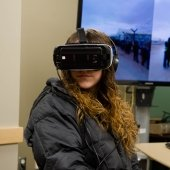 A seated student with a virtual reality headset on in front of a large monitor