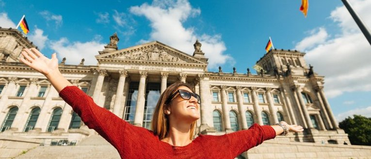 Woman standing in front of a old German Building with arms outstretched, smiling.