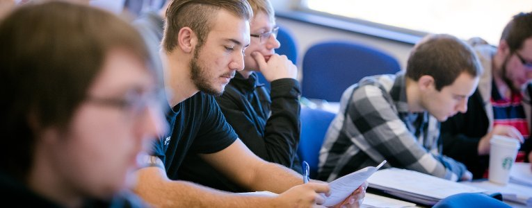 Students sitting in a classroom taking a placement exam.