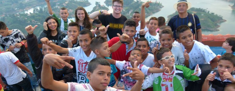 Michigan Tech student in Peru with a group of children posing for a photograph.