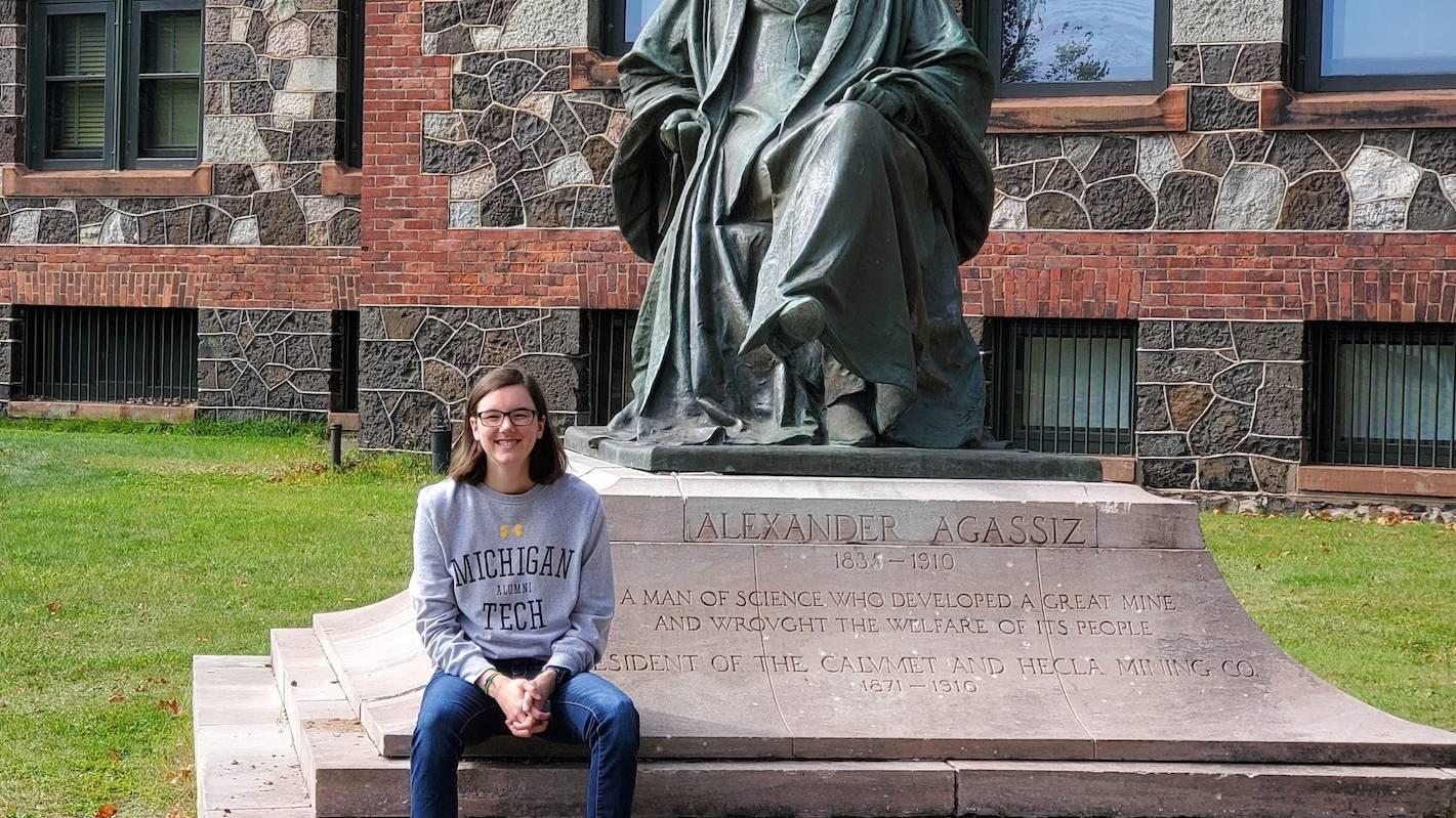 Alum Nicole Bonenfant, wearing an MTU sweatshirt, sits before a statue.