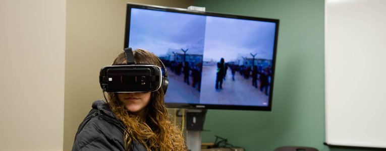 Student sitting with a virtual reality headset in front of a large monitor.