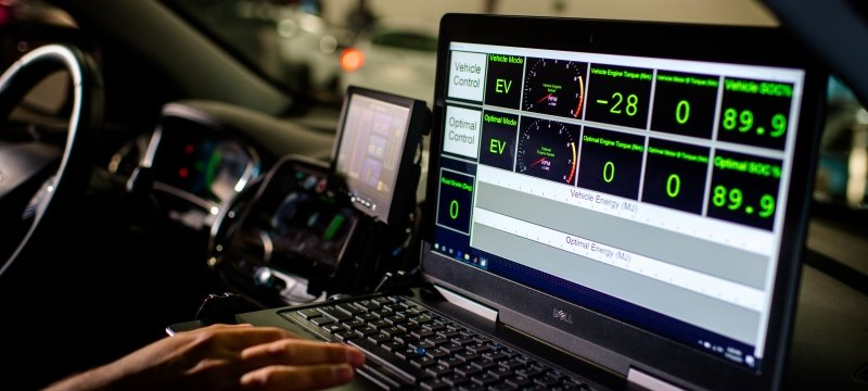 Researcher inside a vehicle with a laptop running diagnostics.