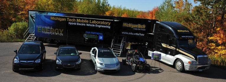 Michigan Tech Mobile Laboratory parked behind four Hybrid Electric Vehicles