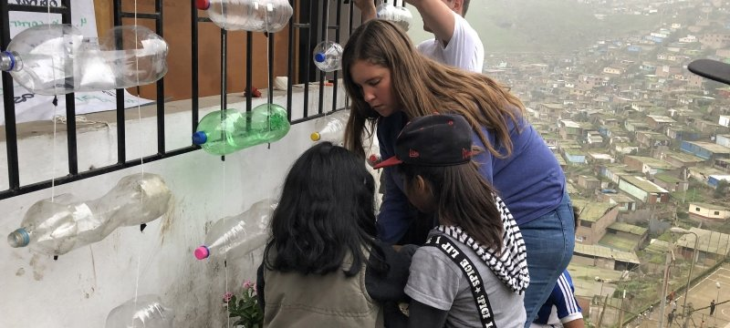 Michigan Tech students help two young Peruvian girls build planters out of upcycled plastic bottles