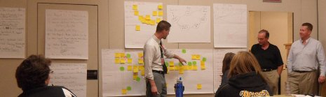 A man gestures to many post-it notes stuck on a wall, in front of a group of people.