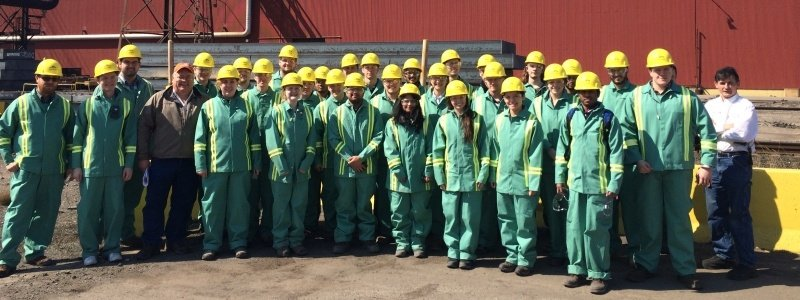 A large group of students, wearing coveralls and hard hats, pose for a photo after an industry tour.