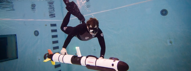 A diver in an indoor pool adjusts an underwater sonar device.