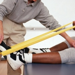Physical Therapist is holding the foot of a patient while they are using a tension band.