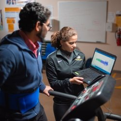 Researcher with laptop, participant on treadmill