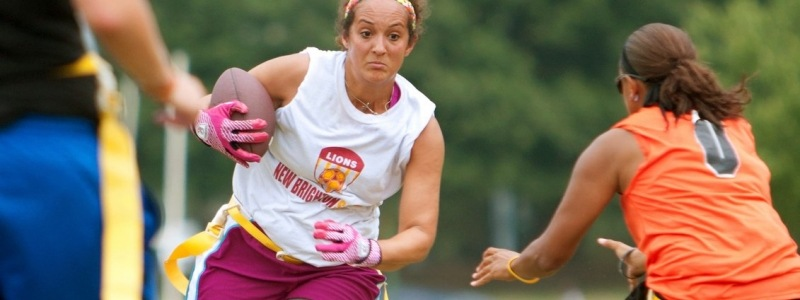 Woman running with football while another attempts to grab her flag during flag football.