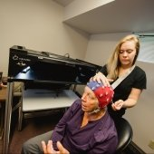 Student researcher fitting a brain monitoring cap on an elderly person's head