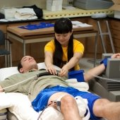 Researcher examining a student in the Integrative Physiology lab