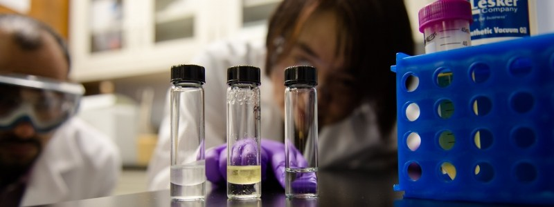 Researchers looking a vials of liquid in a lab.