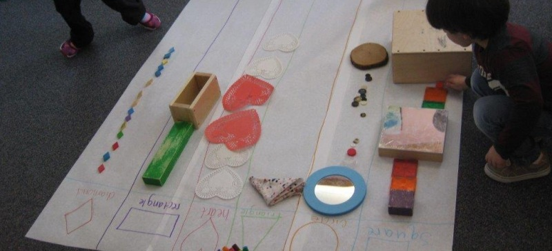 Child sorting objects onto large paper by shape.