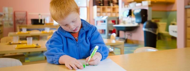 Child sitting at a table drawing with a green marker.