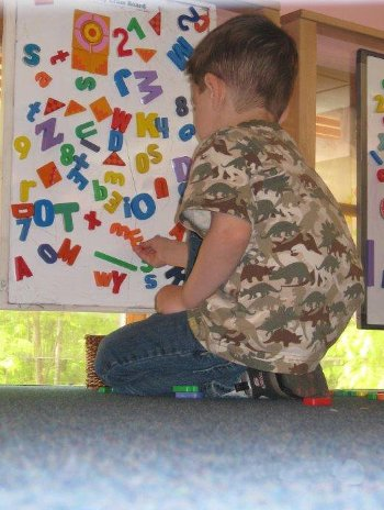 Child plahying with magnetic letters and numbers on a board.