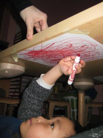 Child laying under a table coloring on a piece of paper taped there.