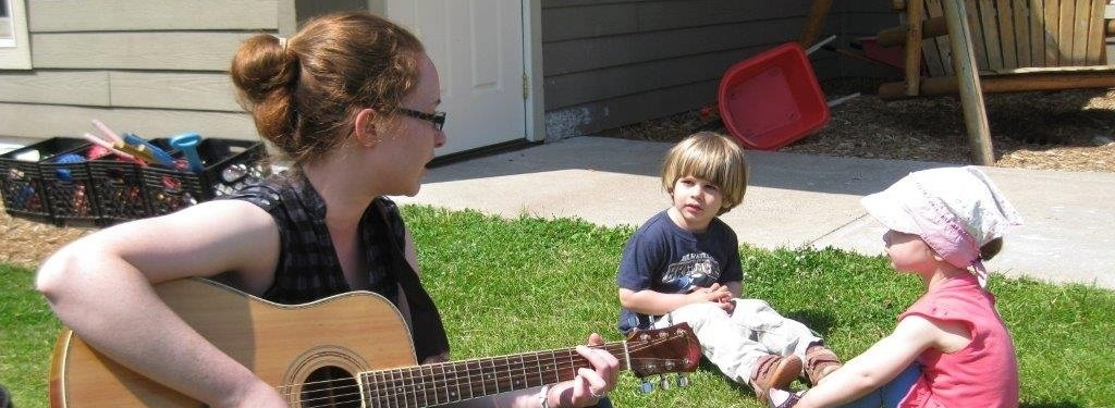 Teacher playing the guitar outside with two children.