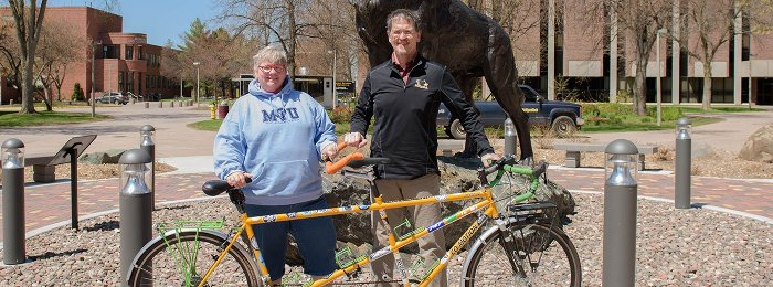 Jim '81 (Civil Engineering) and Shawn '82 (Computer Science) Rathbun with their tandem bicycle in front of the husky statue.