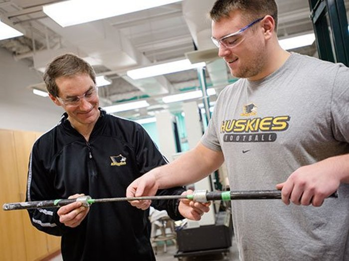 Paul Fraley works with a Michigan Tech student testing Neuvokas rebar.