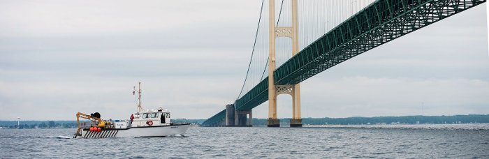 Buoy deployment boat traveling under the Mackinac Bridge.