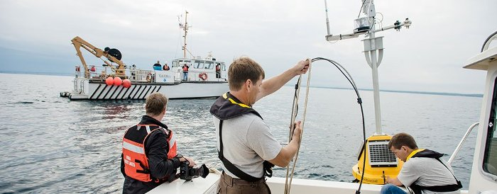 Crews work to deploy a buoy in the Straits of Mackinac.