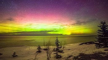 Northern lights over the water in winter.