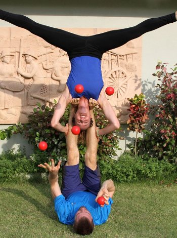 Trish balancing upside-down by her shoulders on Bob's feed while he juggles red balls.