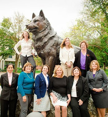 Nine of the twelve new PCA members pose with the husky statue on campus.