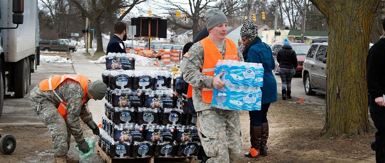 The National Guard distributes water from a pallette to Flint residents.