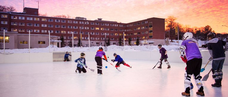 Student playing broomball with Wadsworth Hall and a sunset in the background.