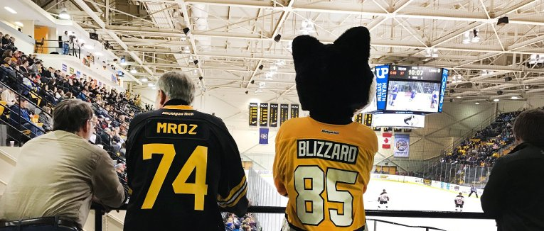 Blizzard and President Mroz watching a hockey game.