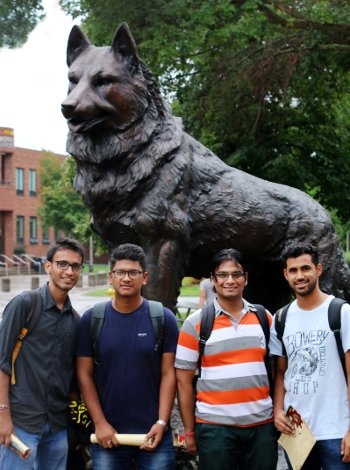 Four international students in front of the husky statue.