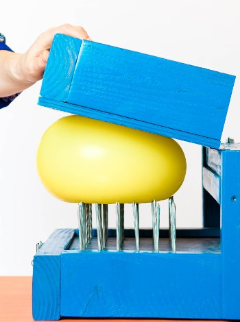 Balloon being pressed onto a bed of nails.