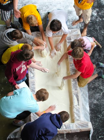 Overhead image of students playing in a tub of oobleck.